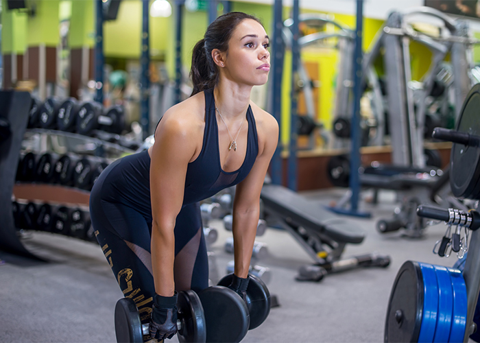 Young woman doing dead lift shoulder exercises in the gym