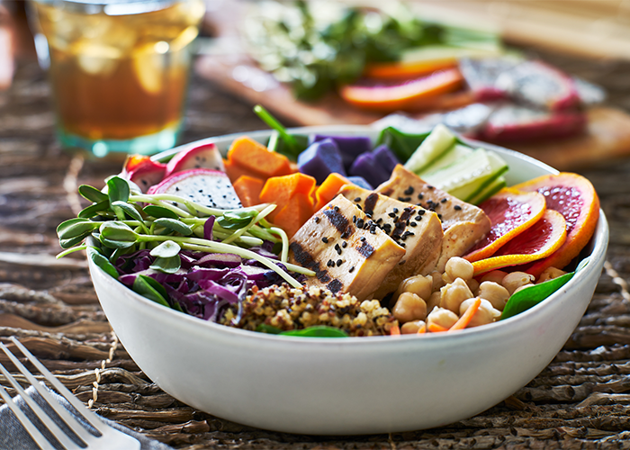 Colorful vegan Buddha bowl with tofu, dragonfruit, sprouts, chickpeas, greens, and pumpkin.
