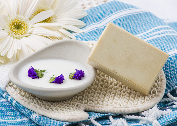 Goat milk soap bar next to a dish with white liquid soap and purple flowers, set on a blue cloth with white flowers behind