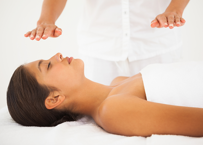 Woman lying on a massage table during a reiki healing session