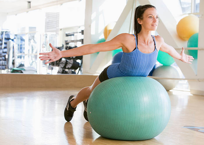 Woman doing balance exercises on an exercise ball