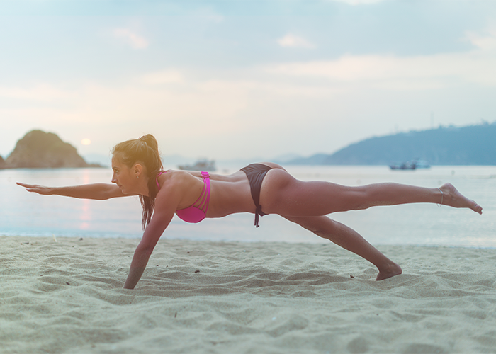 Young woman in bikini doing balance exercises on the beach