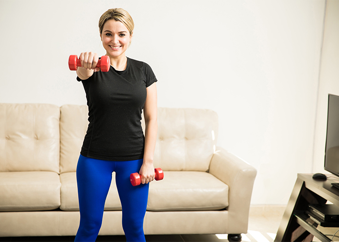 Woman doing shoulder exercises at home with dumbbell