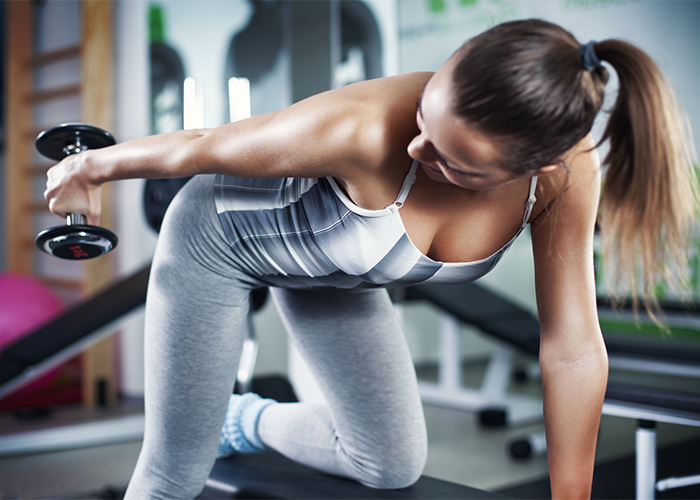 Woman doing exercises with weights for flabby arms