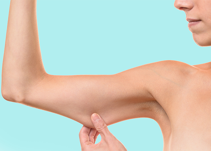 Woman pinching her flabby arm against a pale green background