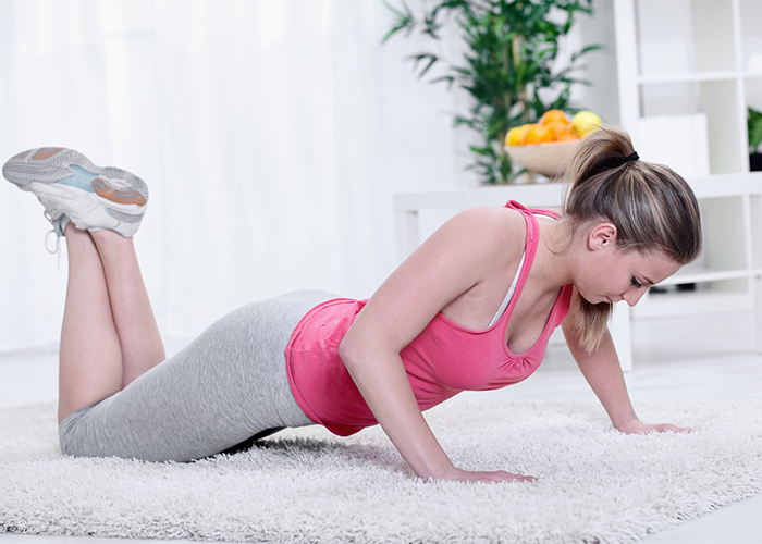 Woman doing push ups at home to rid flabby arms