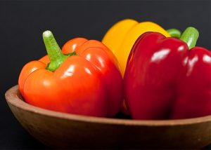 Red, yellow, and orange bell peppers in a bowl