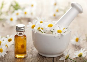 A bottle of chamomile and cedarwood essential oil blend next to a pestle and mortar covered in chamomile flowers