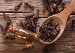 A bottle of clove essential oil surrounded by cloves