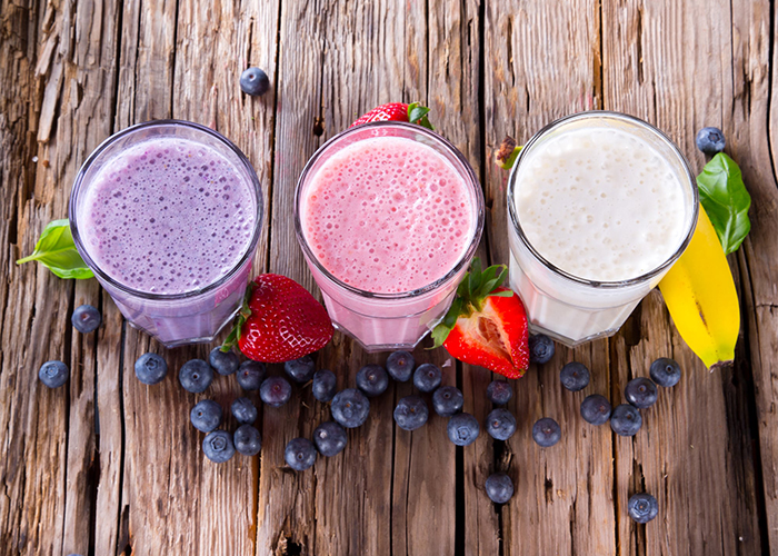 Three glasses of freshly-made fruity keto protein shake: blueberry, strawberry, and banana.
