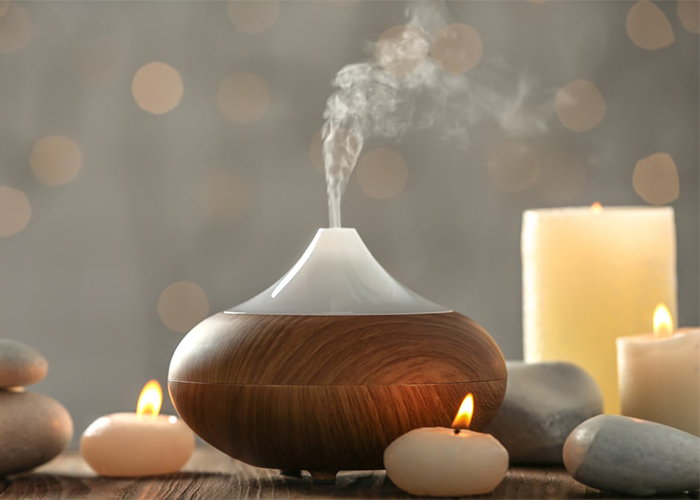 Essential oil blend diffuser for aromatherapy with essential oil candles surrounding it