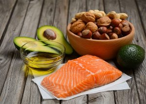 A variety of healthy keto diet fat sources including nuts, avocado, salmon, and olive oil
