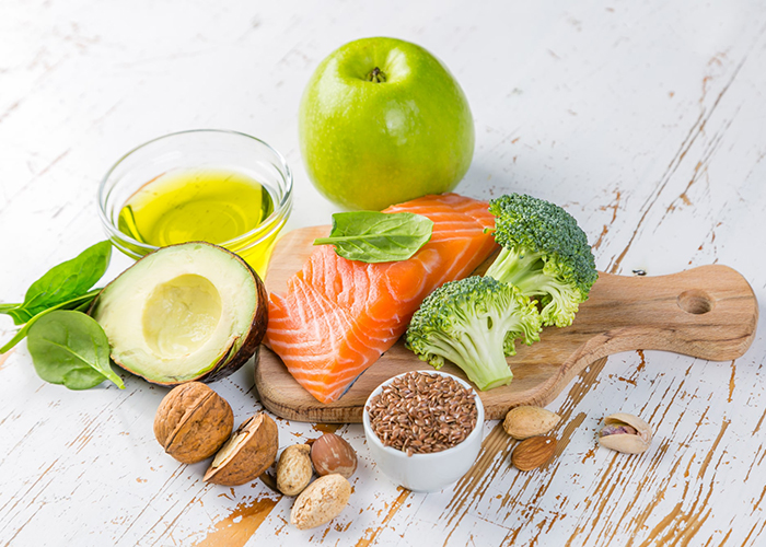 High fat low carb keto diet foods including avocado, salmon, flax seeds, walnuts, an apple, and olive oil