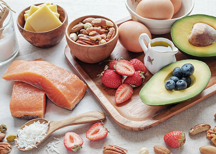 A spread of keto-approved foods that are high in healthy fats and low in carbs such as salmon, cheese, nuts, fruits, eggs, and olive oil