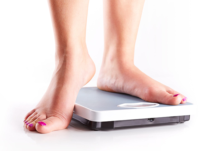 A woman weighing herself on the scale