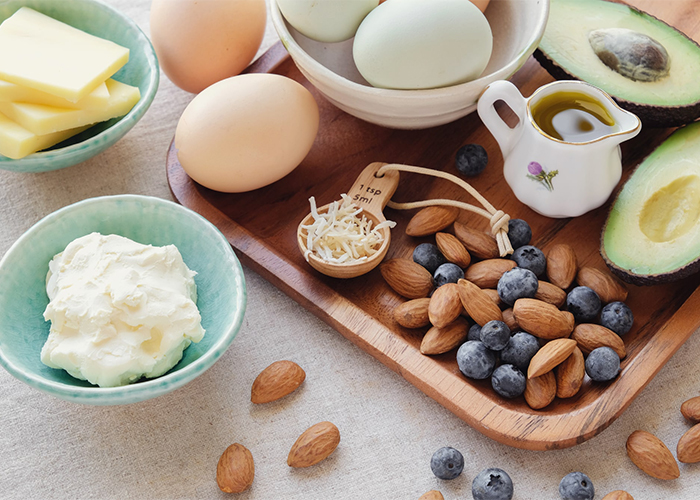 Spread of Ketogenic diet foods including almonds, blueberries, boiled eggs, cream, and avocados