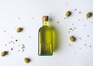 A bottle of olive oil lying flat on a white table, with olives surrounding it