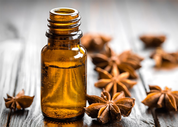 Open bottle of anise essential oil surrounded by dried anise