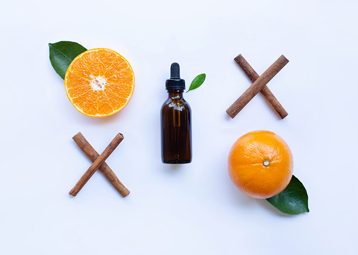 A flat lay of a vial of orange essential oil, cinnamon sticks and fresh oranges