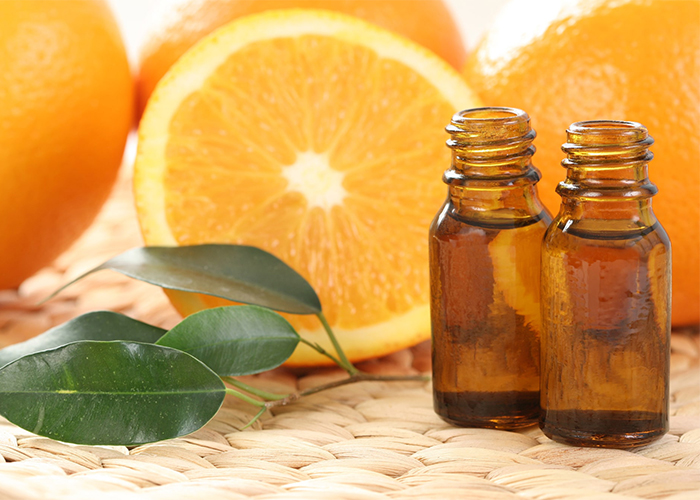 Two vials of orange essential oil in front of fresh oranges
