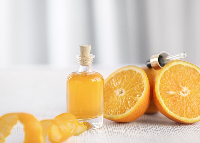 Orange essential oil in clear bottle next to a halved orange and orange rind