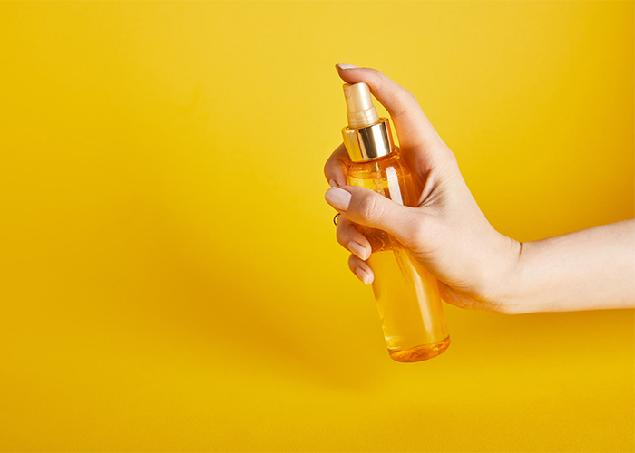 A woman's hand spraying a bottle of orange essential oil mist