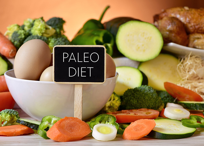 "Sign that says, ""Paleo Diet"" with a background of paleo-approved foods including boiled eggs, carrots, broccoli, and zucchini"