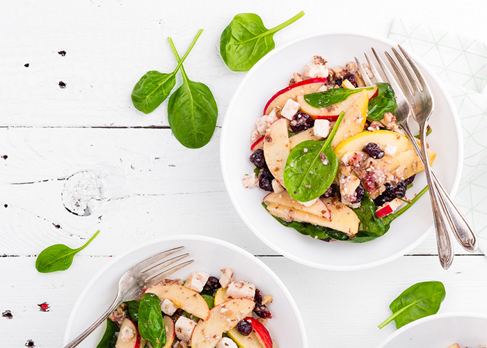 Paleo fruit salad bowls with spinach, apple slices, raisins, and feta cheese