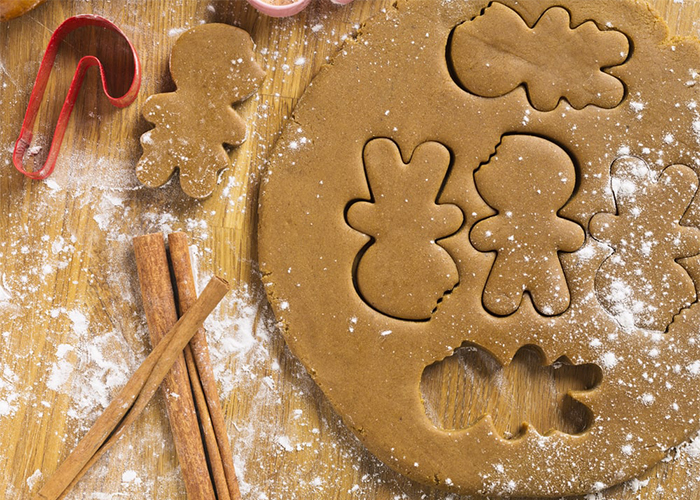 Paleo gingerbread cookie dough being made into in Christmas shapes with cookie cutters