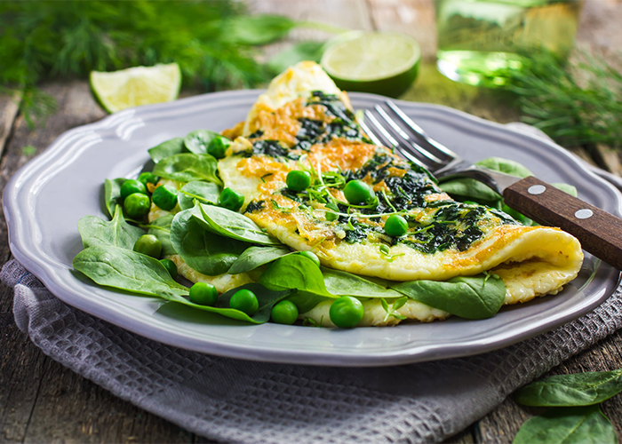 Paleo spinach and egg omelet with a topping of peas
