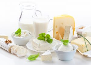 A spread of dairy foods and drinks including cheese, ice cream, butter, and milk