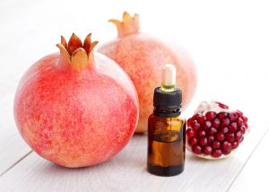 Bottle of pomegranate essential oil for wrinkle-free skin next to two fresh pomegranates