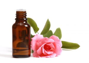 Bottle of anise essential oil blended with rose essential oil next to a fresh rose stem