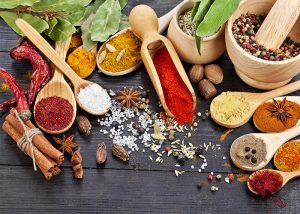 A variety of spices, herbs and salt on a wooden table