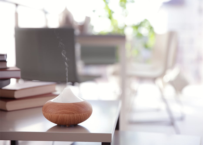 A diffuser on a table with summer essential oil diffuser blends
