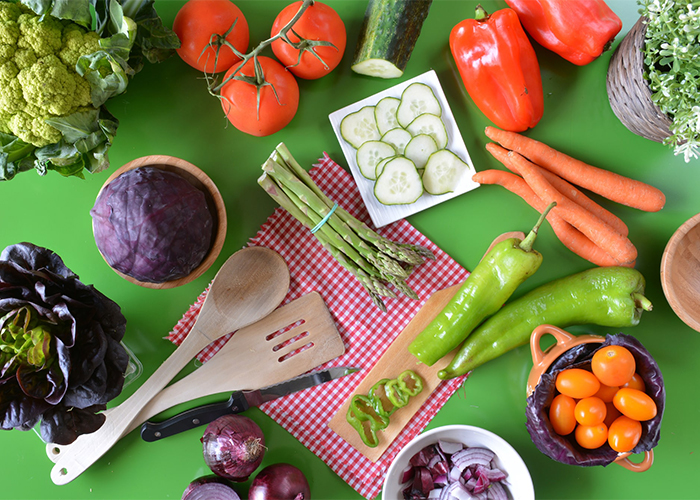 A spread of vegetables such as cabbage, tomatoes, cucumber, peppers, and carrots ready to make a vegetarian meal