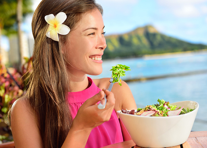 Woman by the seaside eating paleo salad