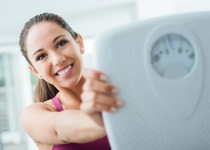 Woman happy with keto weight loss results holding up a scale