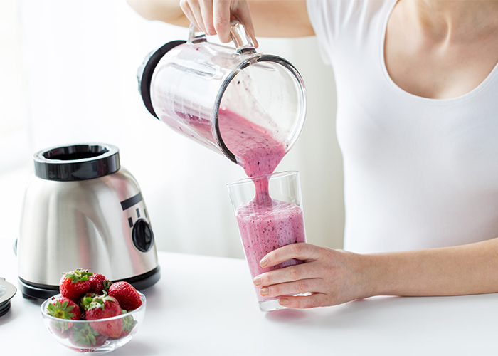 Woman pouring a freshly-blended strawberry keto protein shake into a glass