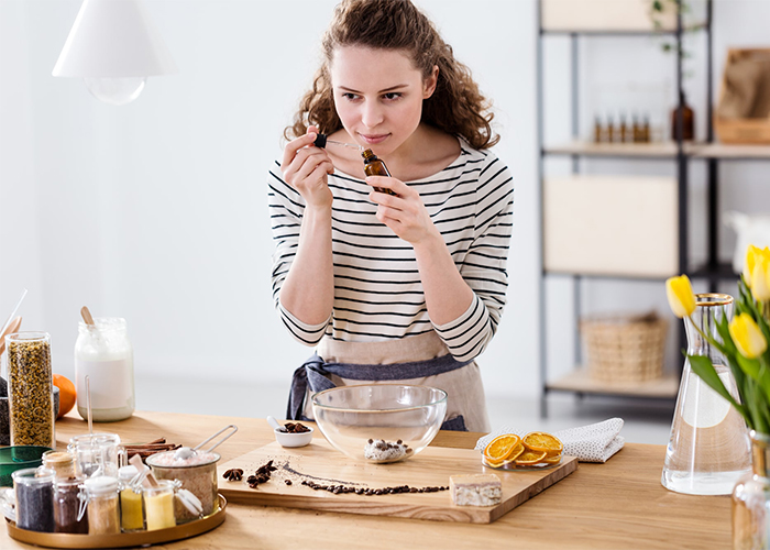 Woman making her own essential oil blends for soap at home