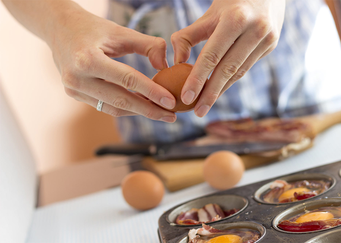 Woman making a Paleo breakfast of egg and bacon muffins