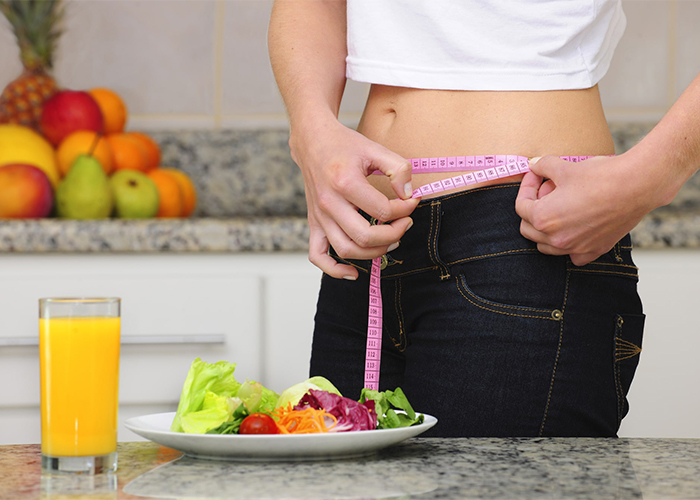 Woman on paleo diet measuring her weight loss with a measuring tape