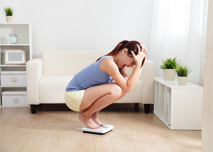 Woman upset at the numbers on the scale as she weighs herself