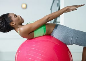 Woman working out on a balance ball to get over keto weight loss plateau