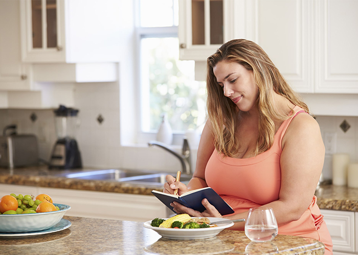 Woman writing in her keto diet journal in her kitchen