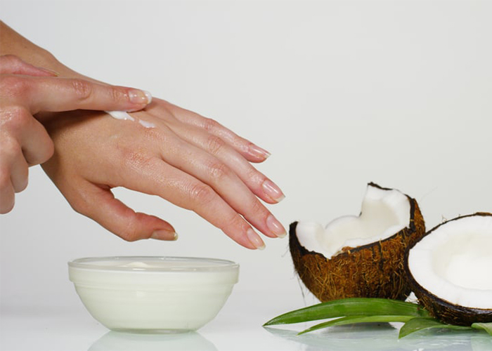 Woman rubbing coconut oil and tea tree essential oil antifungal rub on her hand