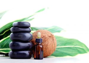 A bottle of coconut essential oil used for aromatherapy next to black stones and a whole coconut