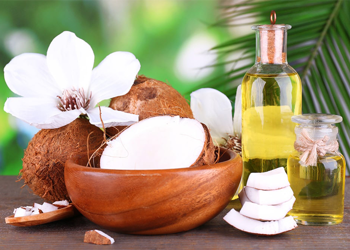 Bottles of coconut oil with fresh coconut for making essential oil products