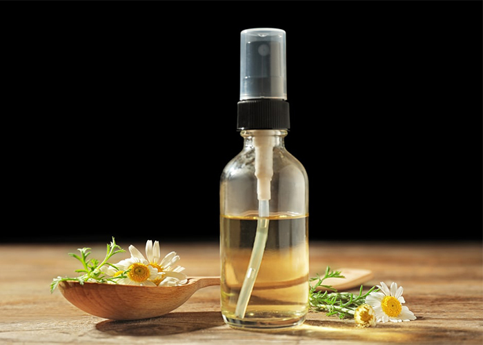 A bottle of homemade essential oil room mist with coconut oil, rosemary essential oil, and bergamot essential oil