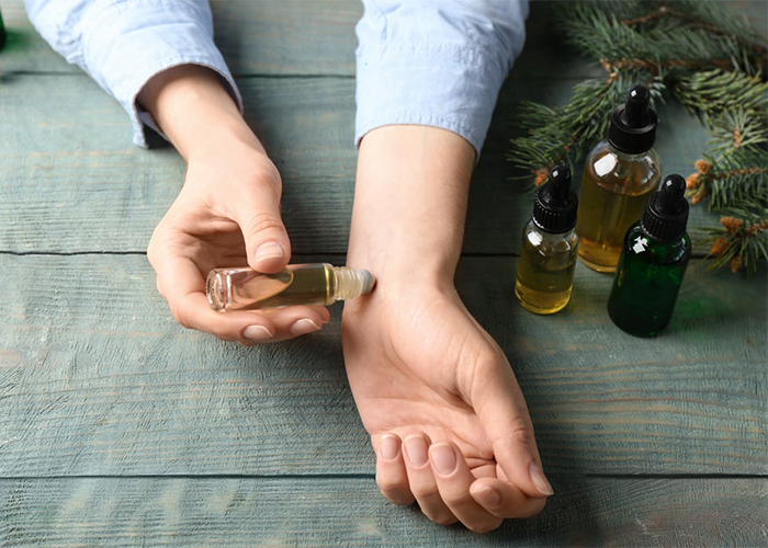 Woman using a homemade essential oil roll-on perfume diluted with coconut oil on her wrist